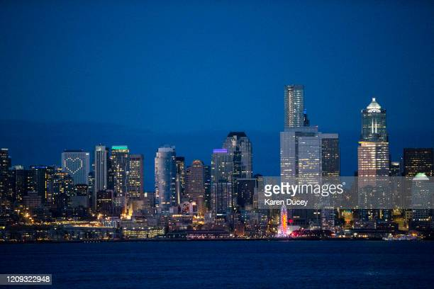 The Seattle skyline is seen at sunset on April 6 2020 in Seattle Washington Windows of the Hyatt Regency Hotel are lit up in the shape of a heart...