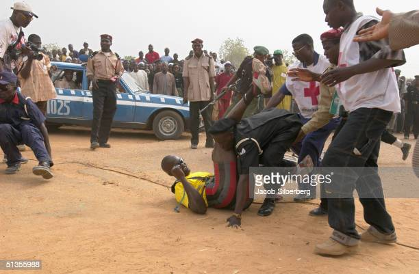 The second place winner in a bicycle race is accidentally trampled by police as he crosses the finish line during the Argungu Fishing Festival on...