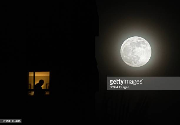 The second super full moon of the year, known as 'flower moon', rises over the sky as a man is seen silhouetted inside a building. The super moon is...