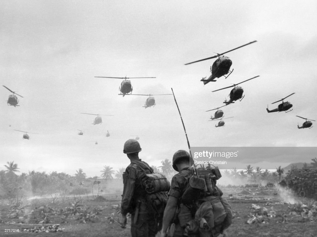The second wave of combat helicopters of the 1st Air Cavalry Division fly over an RTO and his commander on an isolated landing zone during Operation Pershing, a search and destroy mission on the Bong Son Plain and An Lao Valley of South Vietnam, during the Vietnam War. The two American soldiers are waiting for the second wave to come in.