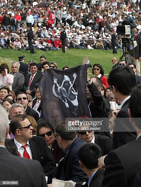 """The Secretary General of the human rights group """"Reporters Without Borders"""" Robert Menard holds a black flag during the speech of China's top Olympic..."""
