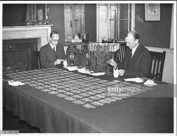 The Secretary of the Royal Almoner and his assistant prepare the purses of Maundy Money at Queen Anne's Gate London These will then be given to the...