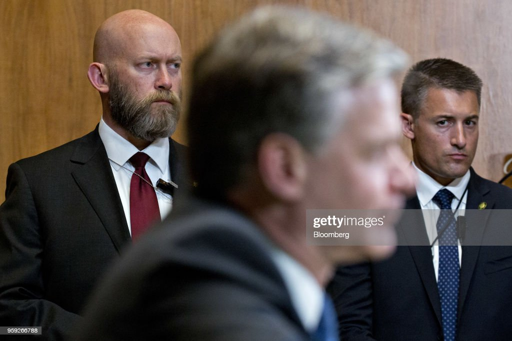 The security detail for Christopher Wray, director of the Federal Bureau of Investigation (FBI), center, stand during a Senate Appropriations Subcommittee hearing in Washington, D.C., U.S., on Wednesday, May 16, 2018. The Subcommittee on Commerce, Justice, Science is reviewing the fiscal year 2019 budget request for the FBI. Photographer: Andrew Harrer/Bloomberg via Getty Images