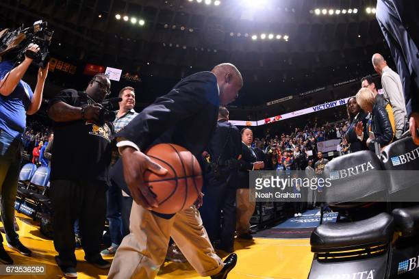 The security guard passes the ball to Stephen Curry of the Golden State Warriors for his pregame shot from the tunnel before the game against the...
