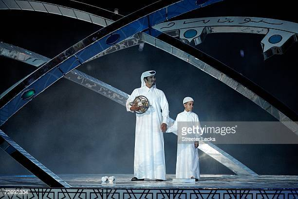 The 'Seeker' and his son stand with the astrolabe onstage during the Opening Ceremony of the 15th Asian Games Doha 2006 at the Khalifa stadium on...