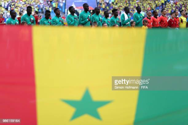 The Senegal team are seen singing their national anthem from behind a Senegal flag prior to the 2018 FIFA World Cup Russia group H match between...