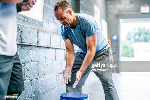 the senior, 55-years-old, athlete preparing for workout with weight, applying a chalk to his palms - 55 59 years stock pictures, royalty-free photos & images