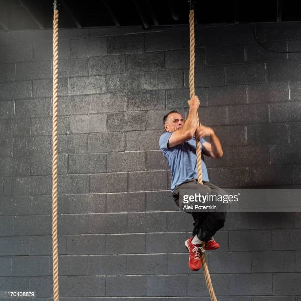 the senior, 55-years-old latino athlete climbing by a rope during the workout - 55 59 years stock pictures, royalty-free photos & images