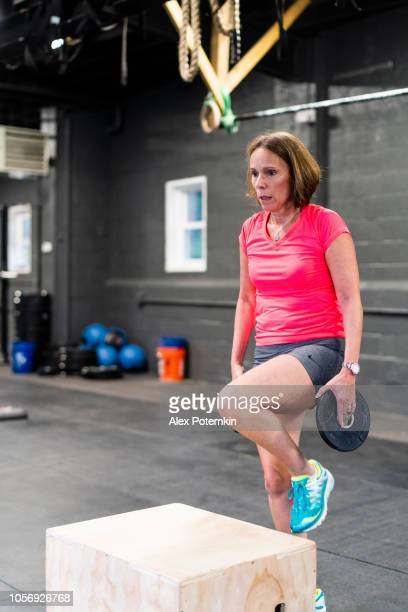 the senior, 55-years-old latino woman doing step-up with weight exercise in the gym - alex potemkin or krakozawr latino fitness stock photos and pictures