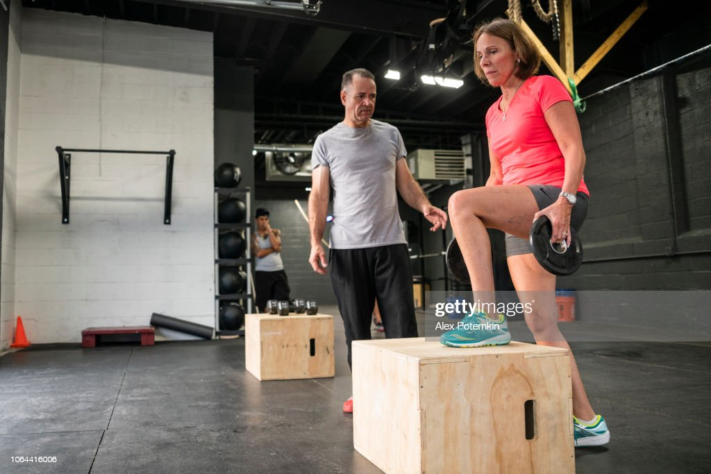 The senior 55-years-old Latino woman doing step-up with weight exercise in the gym : Stock Photo