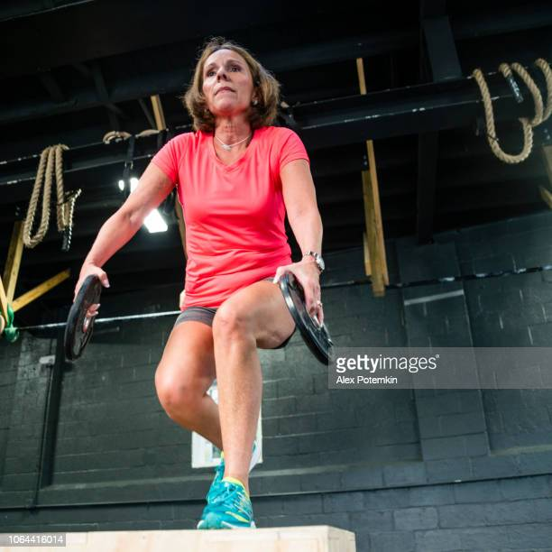 the senior 55-years-old latino woman doing step-up with weight exercise in the gym - alex potemkin or krakozawr latino fitness stock photos and pictures
