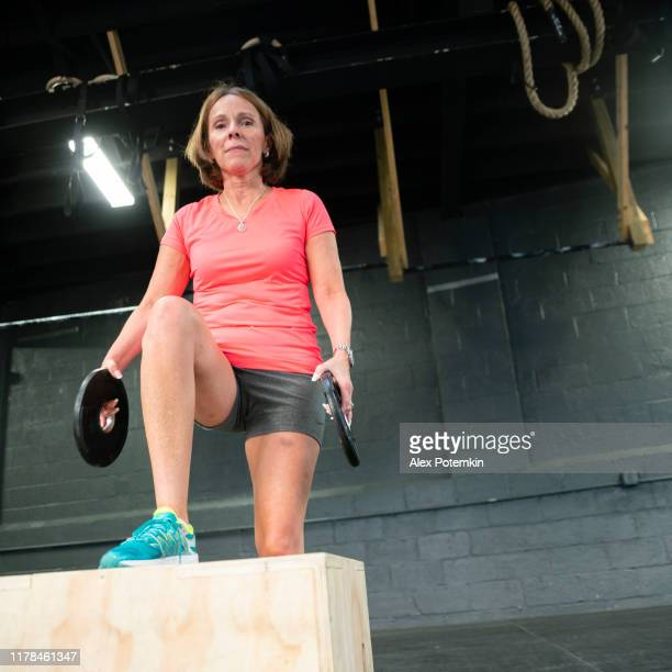 the senior 55-years-old latino woman doing step-up with weight exercise in the gym - 55 59 years stock pictures, royalty-free photos & images