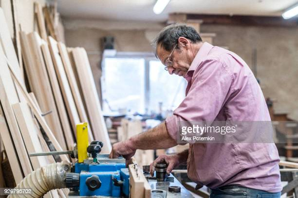 the senior 60-years-old man, carpenter and sashman, craftsman, working with the industrial milling machine at the small wood factory - 55 59 years stock pictures, royalty-free photos & images