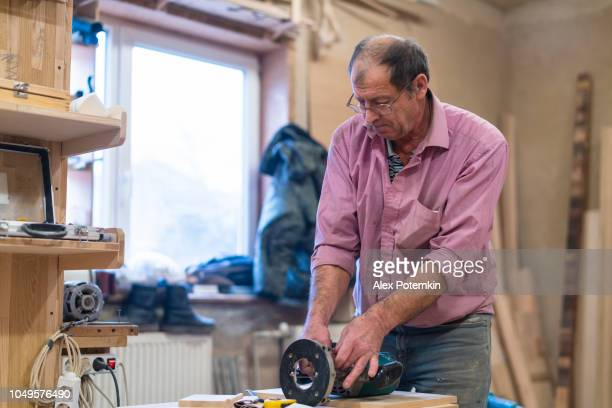 the senior 60-years-old man, carpenter, setting up the manual milling machine. - 55 59 years stock pictures, royalty-free photos & images