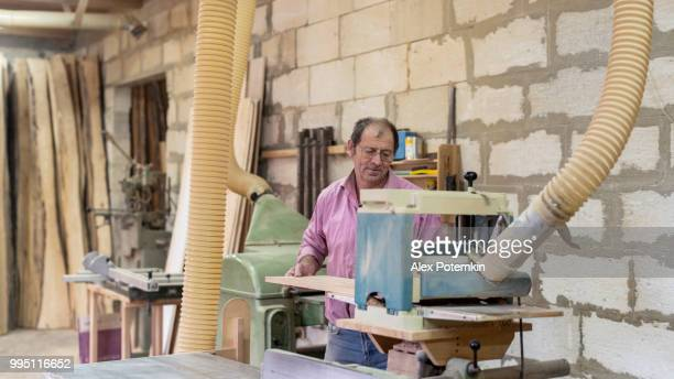 the senior 60-years-old man, the carpenter, working with the industrial grinding machine at the small furniture factory - 55 59 years stock pictures, royalty-free photos & images