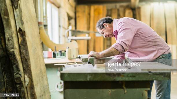 the senior 60-years-old man, the joiner, working with the commercial circular saw machine at the small furniture factory - 55 59 years stock pictures, royalty-free photos & images