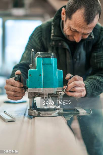 the senior 65-years-old craftsman working with the electric hand milling machine. woodworks on the small furniture factory. - 65 69 years stock pictures, royalty-free photos & images