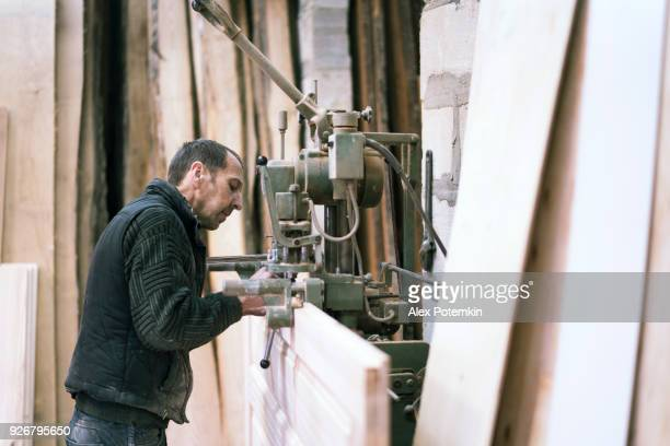 The senior 65-years-old man, sashman and carpenter, working with the industrial chain milling machine at the small wood manufacture