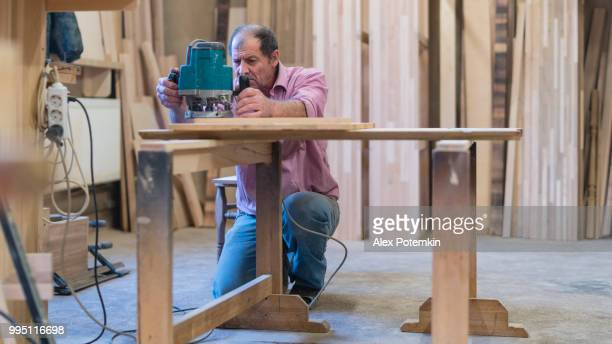 the senior 65-years-old man working with the electric hand milling machine. woodworks on the small furniture factory. - 55 59 years stock pictures, royalty-free photos & images