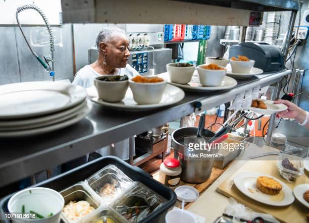 the senior active entrepreneur businesswoman, african-american, checking out the kitchen of her restaurant - working seniors stock pictures, royalty-free photos & images