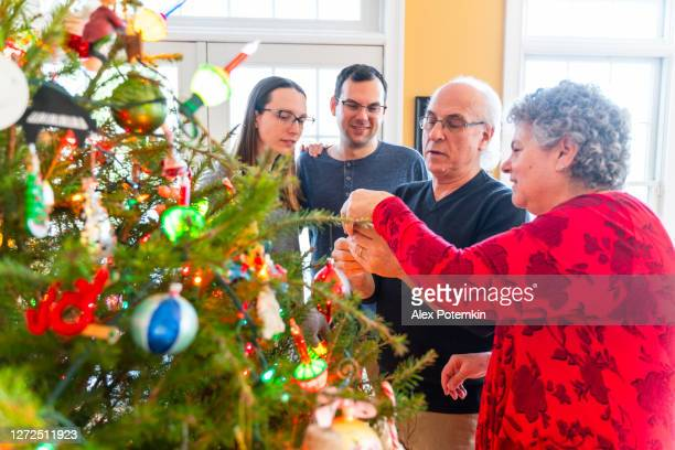 the senior couple, a 73-years-old man and 65-years-old woman, decorating christmas tree together with their adult kids. - 65 69 years stock pictures, royalty-free photos & images
