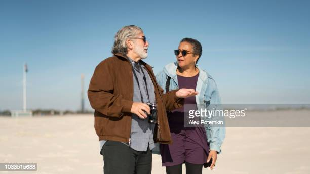 The senior couple, African-American woman and silver haired, bearded White man, walking at the Jones Beach