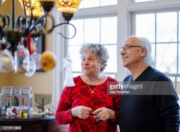 the senior couple decorating their house for the winter holidays, both christmas and hanukkah. - judaism stock pictures, royalty-free photos & images