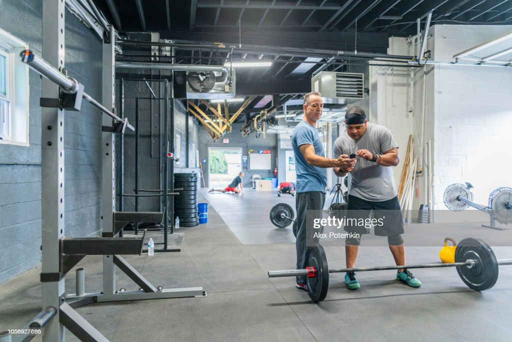 The senior Latino man, the coach, showing the fitness results to the young Hispanic athlete, powerlifter, on a smart fitness device in the gym during the workout. : Stock Photo