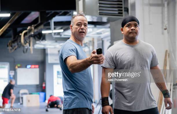 The senior Latino man, the coach, showing the fitness results to the young Hispanic athlete, powerlifter, on a smart fitness device in the gym during the workout.