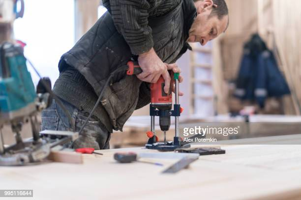 The senior man, carpenter, drilling the wooden detail at the small furniture factory