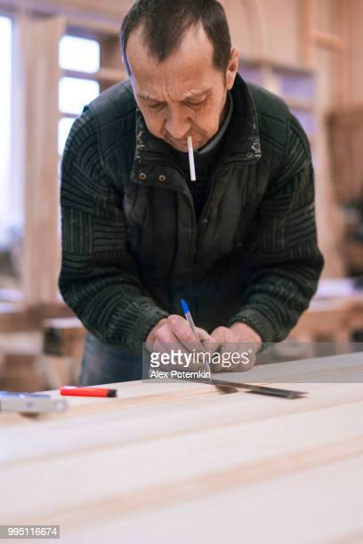 The senior man, carpenter, measuring and marking up a wooden detail for further processing.