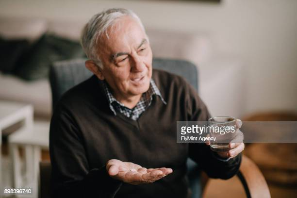 The senior man holding pills in one hand and water in the other one