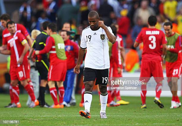The Serbia team celebrate victory as Cacau of Germany looks dejected after the 2010 FIFA World Cup South Africa Group D match between Germany and...