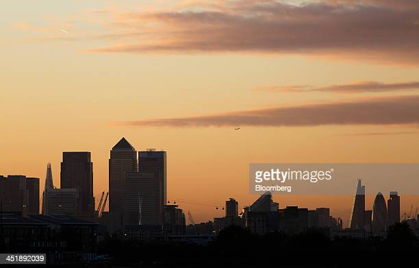 The setting sun colors the sky orange above the headquarters of Barclays Plc and HSBC Holdings Plc in the Canary Wharf business and financial...