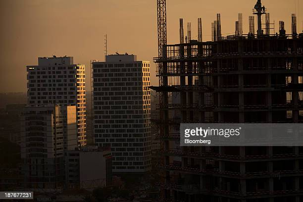 The setting sun illuminates a construction site beyond commercial office buildings in central Luanda Angola on Thursday Nov 7 2013 Angola the largest...