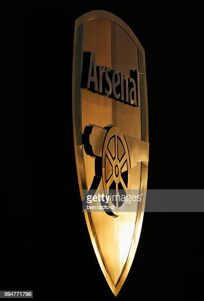 The setting sun is reflected in the Arsenal club crest attached high to the side of the recently finished Emirates Stadium home of Arsenal Football...