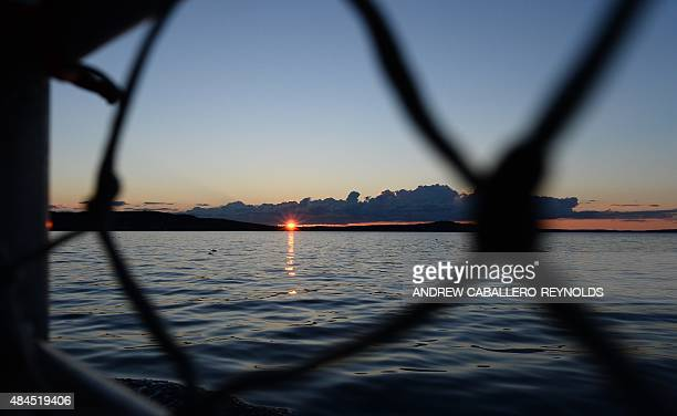 The setting sun is seen from a boat near Mount Desert island in Bar Harbor Maine on August 13 2015 AFP PHOTO/ ANDREW CABALLEROREYNOLDS