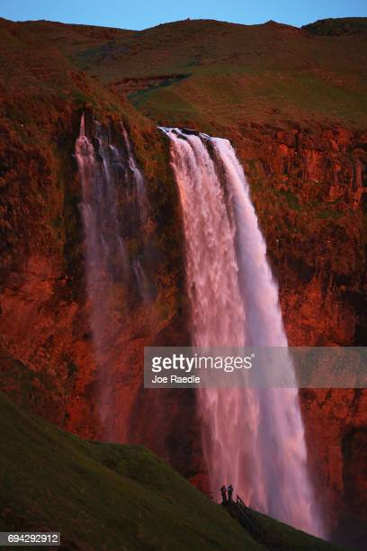 The setting sun lights up the waterfall known as Seljalandsfoss with a red glow on June 4 2017 in Selfoss Iceland Iceland's tourism industry...