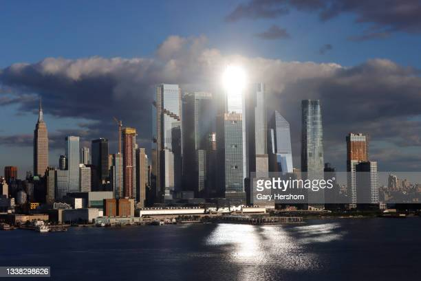 The setting sun reflects off the windows of 50 Hudson Yards and the Empire State Building in New York City on September 3, 2021 as seen from...