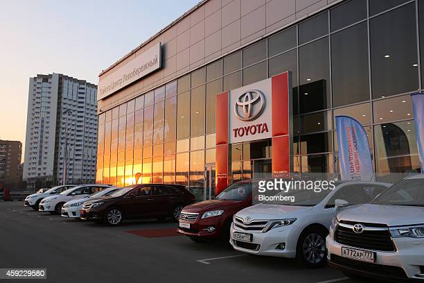 The setting sun shines on the showroom windows of a Toyota Motor Corp automobile dealership in Moscow Russia on Tuesday Nov 18 2014 A recession is...