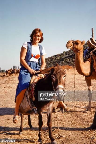 den siebziger jahren. eine junge frau genießen sie ihren urlaub in der türkei von einem esel reiten. - dia stock-fotos und bilder