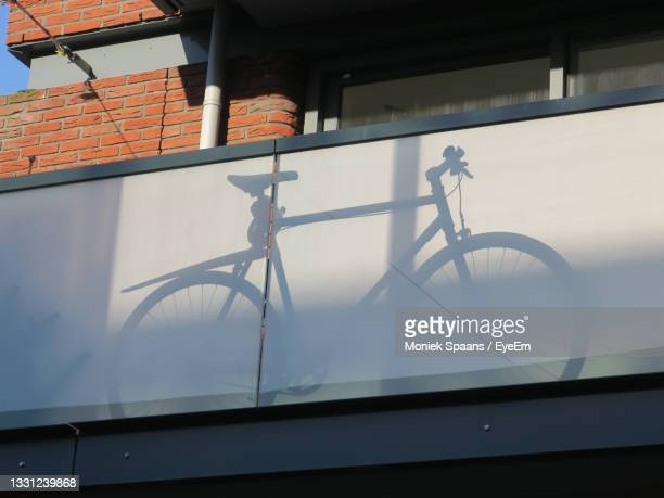the shadow of a bicycle placed behind glass on a balcony - moniek spaans stockfoto's en -beelden