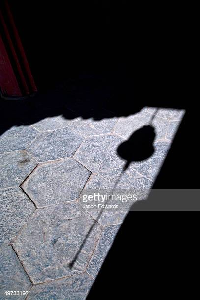 The shadow of a brass bell and chain hanging in a doorway to a Buddhist monastery.