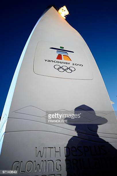 The shadow of a Canadian police officer is seen on the torch in Whistler during the Vancouver Winter Olympics on February 14 2010 AFP PHOTO / FRANCK...