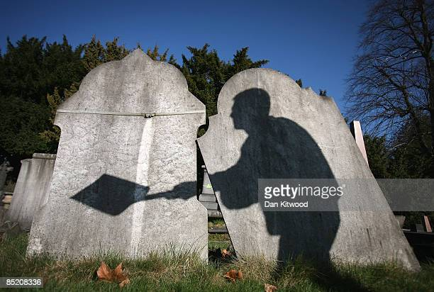 The shadow of a cemetery worker is cast on reclaimed gravestones in London City Cemetery on March 2 2009 in London England The cemetery is piloting a...
