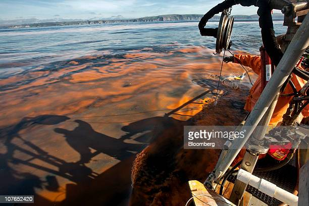 The shadow of a crew member on the Outsider a commercial crabbing boat is seen in the red algae off the coast of Bodega Bay California US on Saturday...
