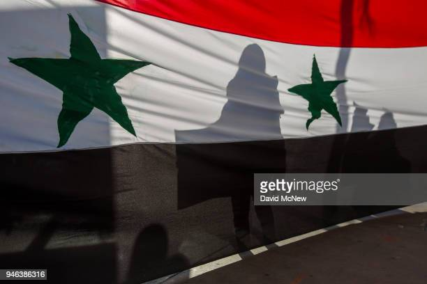 The shadow of a demonstrator is seen through a Syrian flag as supporters of Syrian president Bashar alAssad protest the USled coalition attack in...