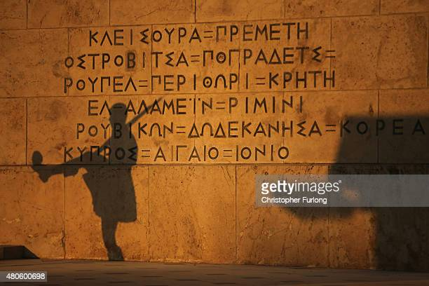 The shadow of a Greek Presidental Evzoni guard falls on the parliament building as protesters gather to demonstrate against austerity after an...