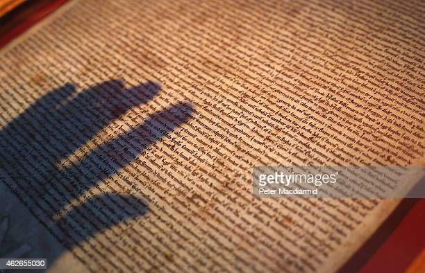 The shadow of a hand hovers over The Salisbury Magna Carta on display at the British Library on February 2 2015 in London England Magna Carta one of...