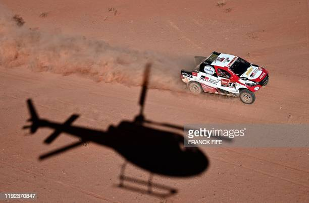 TOPSHOT The shadow of a helicopter is cast as Toyota's driver Fernando Alonso of Spain and codriver Marc Coma of Spain compete during the Stage 3 of...